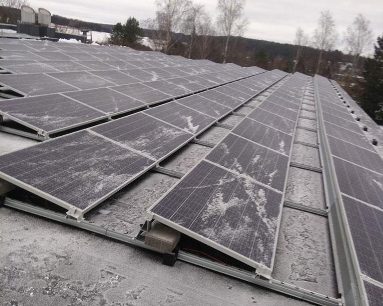 Aurinkopaneelit rakennuksen katolla talvella