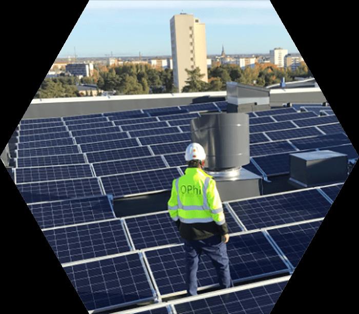 Työmies seisoo rakennuksen aurinkopaneeleilla päällystetyllä katolla
